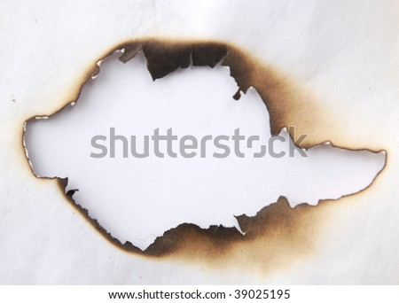 close up view of a burnt hole in a paper - stock photo