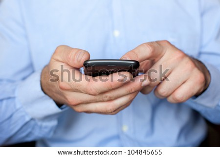 Close up view of a businessman using a smartphone - stock photo