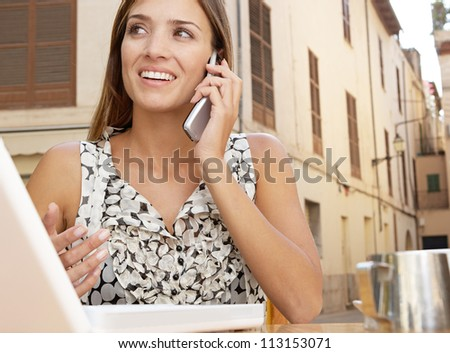 Close up view of a businesswoman making a phone call and using a laptop computer while having a coffee in a coffee shop terrace, outdoors.