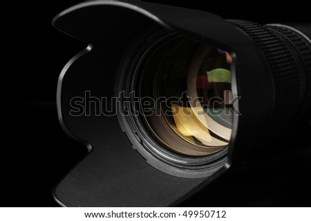 Close-up view of a camera telephoto lens in a black background