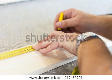 Close Up view of a carpenter using a straightedge to draw a line. - stock photo