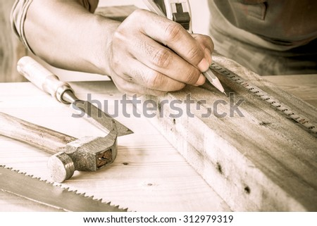 Close Up view of a carpenter using a straightedge to draw a line on a board. - stock photo