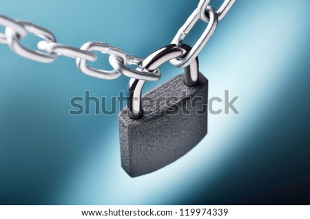 Close-up view of a closed chain with a padlock on blue background