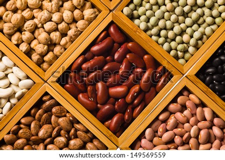 Close up view of a collection of various beans contained in wood boxes.