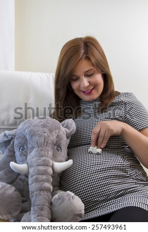 Close up view of a expecting pregnant happy woman holding a tiny car toy. - stock photo