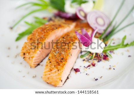 close-up view of a garnished salmon fillet dish - stock photo