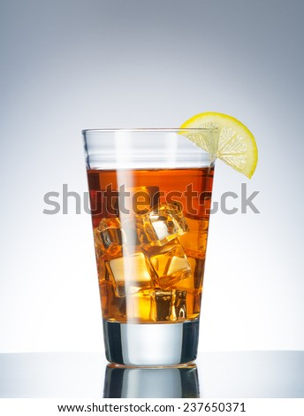 close up view of a glass with iced tea and lemon on blue back