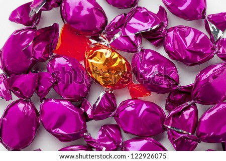 Close-up view of a golden candy surrounded by purple hard candies over white background. - stock photo