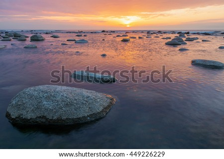 Close-up view of a granite stone in the calm water of the sea at the evening