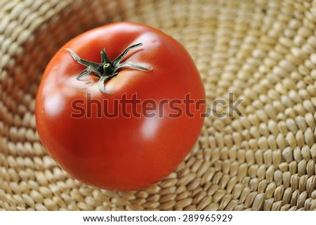 close-up view of a juicy red tomato in wicker basket, shallow DOF - stock photo