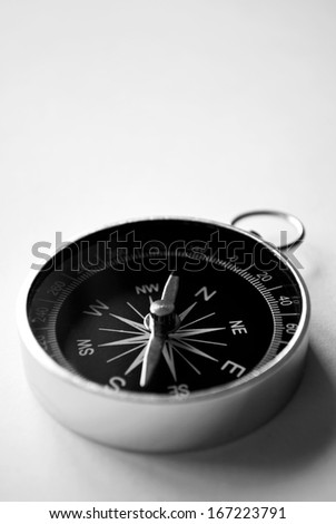 Close up view of a magnetic handheld compass with copyspace showing the needle, compass rose and cardinal points conceptual of planning, navigation, discovery, travel and strategy - stock photo