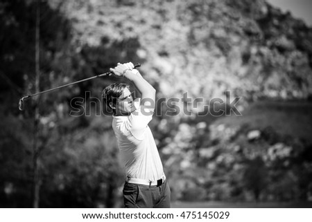 Close up view of a male golfer on a golf course on a bright sunny day.