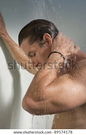 Close up view of a man having a shower and leaning on the wall. - stock photo