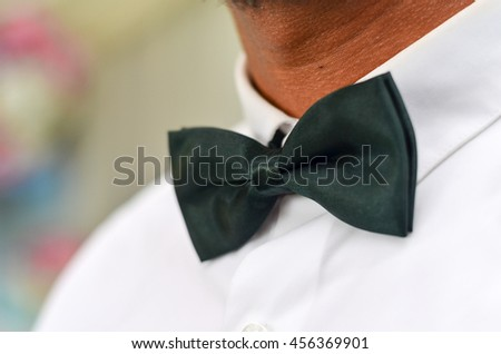 Close up view of a man with his bow tie, wearing white shirt. Selective focus and shallow DOF.