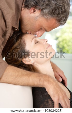Close up view of a mature man kissing woman's forehead while lounging at home's living room.