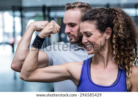 Close up view of a muscular couple flexing biceps - stock photo