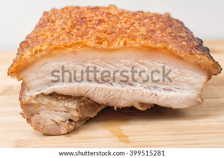 Close Up View Of A Piece Of Chinese Roasted Pork Belly On Wooden Cutting Board