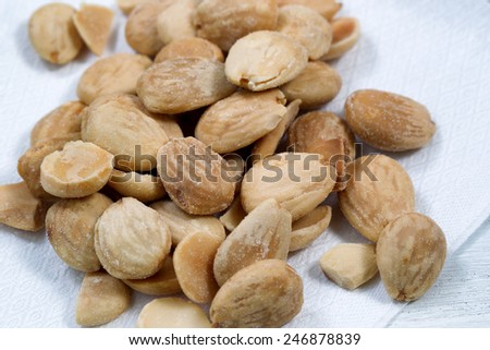 Close up view of a pile of salted almonds on white cloth napkin. Focus front middle of pile.  - stock photo