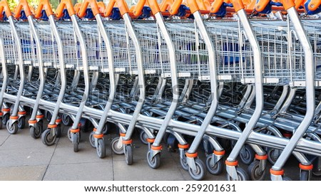 Close-up View of a Row of Stacked Supermarket Trolleys - stock photo