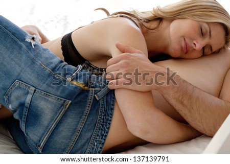 Close up view of a sexy couple laying down in bed, relaxing and hugging in intimacy. - stock photo