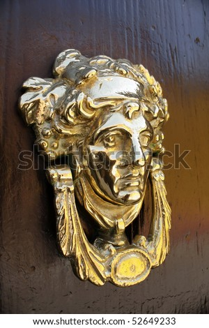 Close up view of a traditional brass door knocker on a door in the Mexican city of San Miguel Allende. - stock photo