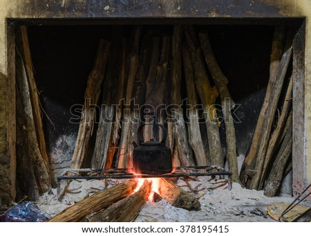 Close-up view of a traditional fireplace/kitchen with bunch of burning firewood to boil water in the old aluminum kettle. This ancient cooking way is still retain in many countryside of Viet Nam. - stock photo
