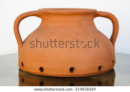 Close up view of a traditional portuguese clay pot for cooking chestnuts.  - stock photo