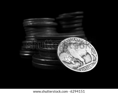 Close up view of a United States Buffalo Nickel with stacks of coins behind it on a black background. - stock photo