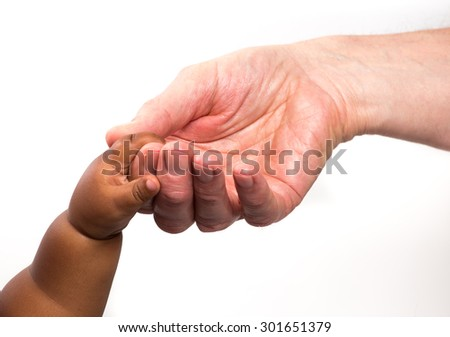 Close up view of a white / caucasian man holding a black / african baby's hand - stock photo
