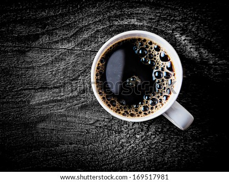 Close up view of a white mug of fresh full roast filter coffee or espresso with frothy bubbles on a grungy weathered wooden surface with vignetting and copyspace - stock photo