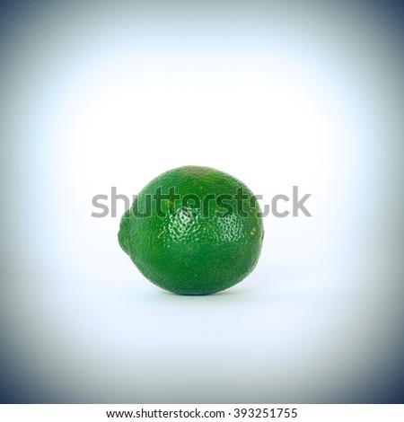 Close-up view of a whole fresh green organic raw lemon isolated on white background with clipping path. vignette effect added.