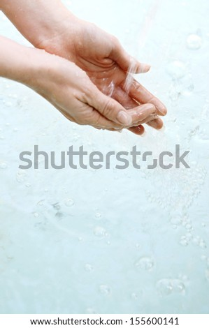 Close up view of a woman hands held together under the falling cleansing water of a spa fountain during a sunny day outdoors.