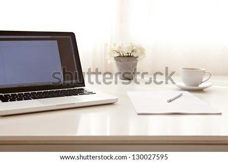 Close up view of a work desk interior with a laptop computer, a cup of coffee and white curtains on a sunny day. - stock photo