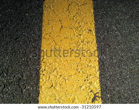 Close up view of a yellow road stripe.