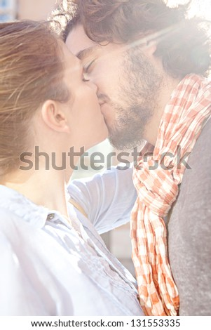 Close up view of a young attractive bohemian couple kissing outdoors with the sun rays filtering through during a sunny day. - stock photo