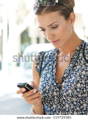 Close up view of a young businesswoman using a smart phone while standing in a classic city busy street.