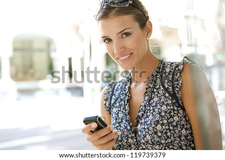 Close up view of a young businesswoman using a smart phone while standing in a classic city street.
