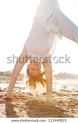Close up view of a young girl doing cartwheels on a golden sand beach with the sun rays filtering through her body during sunset. - stock photo