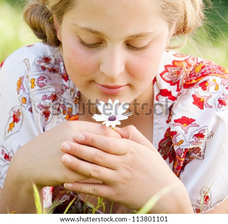Close up view of a young teenager holding a white daisy flower while laying down on a green grass garden, smelling it. - stock photo