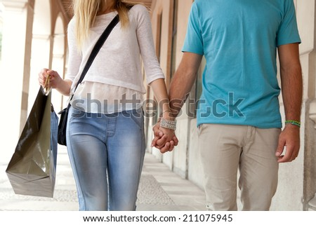 Close up view of a young tourist couple shopping and walking together holding hands while visiting a destination city on holiday in a classic city shopping mall store, relaxing. - stock photo