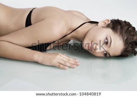 Close up view of a young woman laying down on a reflective surface wile wearing a black swimming costume and smiling.