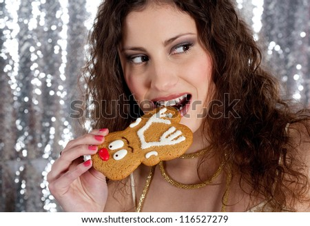 Close up view of a young woman taking a bite off a Christmas reindeer biscuit with a silver sequins background.