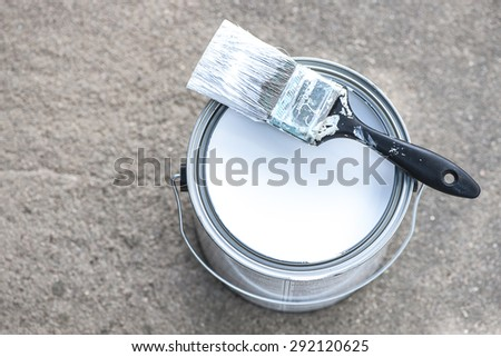 Close-up view of aluminum paint can on concrete with white paint and dirty paint brush, shallow DOF - stock photo