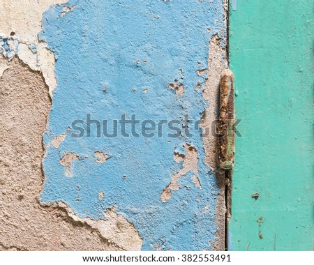 Close-up view of an aged green wooden window shutter with a rusty old-fashioned metal hinge. It hooked with an ancient blue painted wall with cracked stucco layer. Vintage urban background in Vietnam. - stock photo