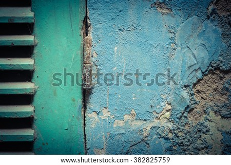 Close-up view of an aged green wooden window shutter with a rusty old-fashioned metal hinge. It hooked with an ancient blue painted wall with cracked stucco layer. Vintage urban background in Vietnam.
