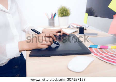 Close up view of an artist drawing something on graphic tablet at the office - stock photo