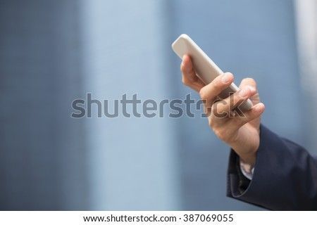 Close-up view of an Asian businessman using digital smart phone in the city. Horizontal view. - stock photo