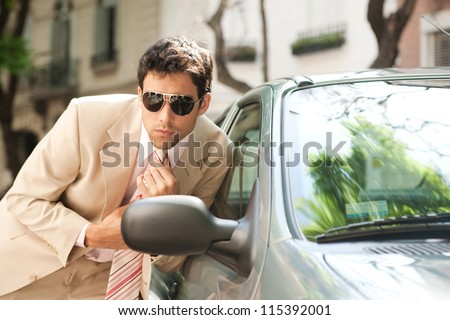 Close up view of an attractive businessman grooming himself using a car mirror outdoors, tightening his tie knot. - stock photo