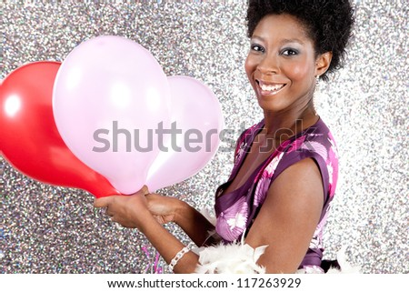 Close up view of an attractive young black woman holding pink and red balloons against a silver glitter background, smiling. - stock photo