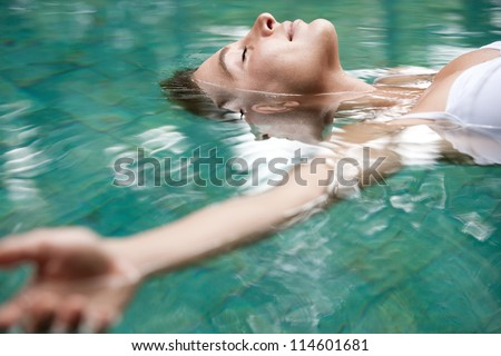 Close up view of an attractive young woman floating on a spa's swimming pool, smiling. - stock photo